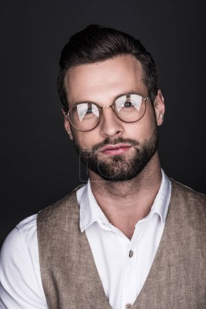 portrait of handsome confident man in glasses and stylish vest, isolated on grey