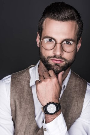 portrait of thoughtful bearded man posing in trendy eyeglasses, isolated on grey