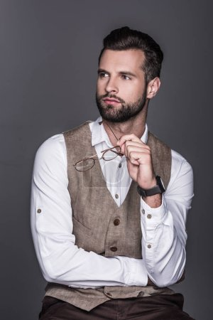 portrait of handsome bearded man holding glasses and posing in waistcoat, isolated on grey