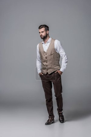 handsome bearded man posing in trendy elegant waistcoat on grey