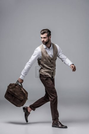 hurry stylish man running with leather bag on grey