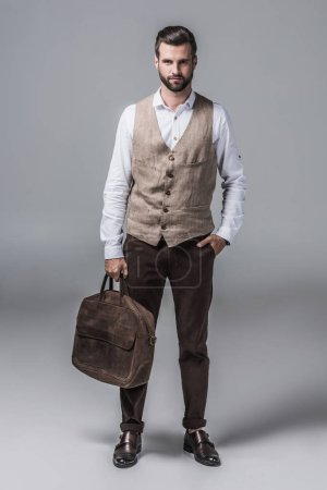 handsome elegant man posing with leather bag on grey