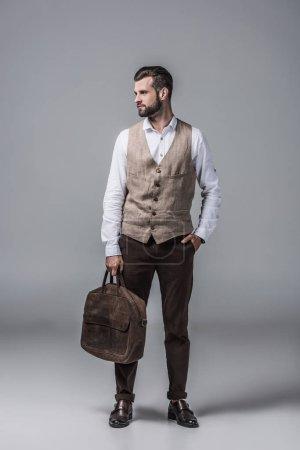 stylish elegant man in waistcoat posing with leather bag on grey