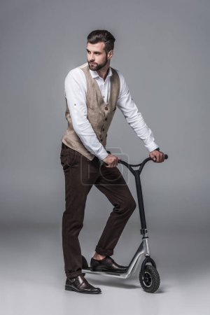Photo for Stylish elegant young man posing on modern scooter on grey - Royalty Free Image