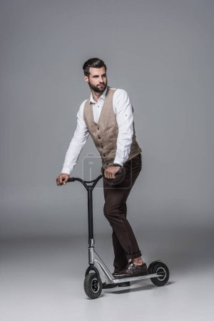 stylish elegant bearded man on modern scooter on grey