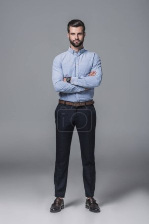 confident stylish business man posing with crossed arms, on grey