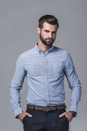 elegant stylish businessman posing in formal wear, isolated on grey