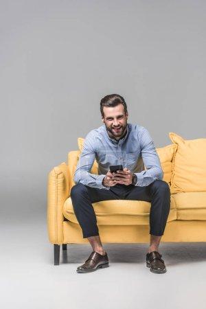 Photo pour Homme joyeux en utilisant smartphone et assis sur un canapé jaune sur gris - image libre de droit
