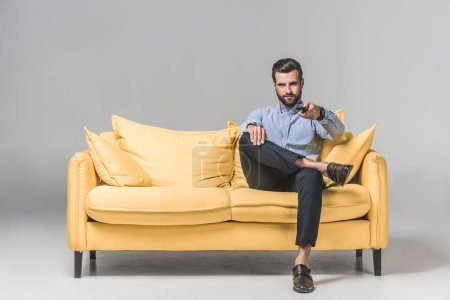 handsome smiling man with remote control watching TV and sitting on yellow sofa on grey