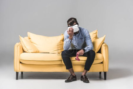 upset man lost in video game with joystick and virtual reality headset on yellow sofa on grey