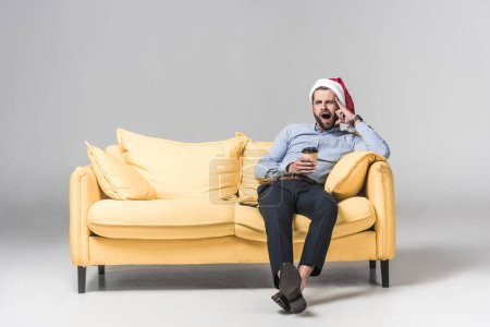 tired man in santa hat yawning, holding coffee to go and sitting on yellow sofa on grey