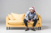 excited man in santa hat playing video game with joystick while sitting on sofa on grey