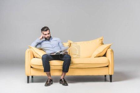upset businessman reading newspaper while sitting on yellow sofa, on grey