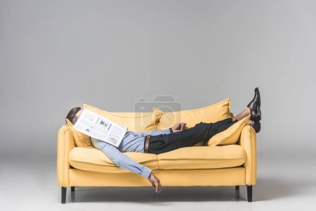 tired businessman sleeping on yellow sofa with newspaper on face, on grey