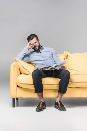 confused businessman with newspaper sitting on yellow sofa, on grey