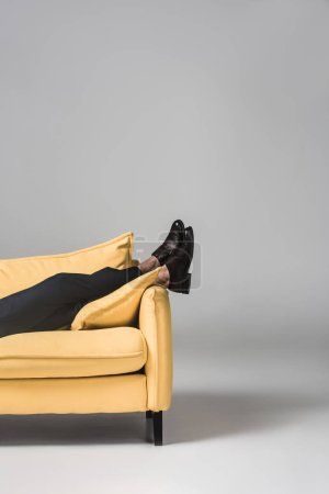 Photo for Cropped view of male legs lying on yellow sofa on grey - Royalty Free Image