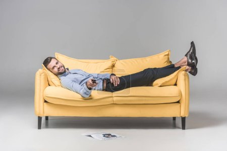 smiling man with remote control watching TV and lying on sofa with newspaper on floor, on grey