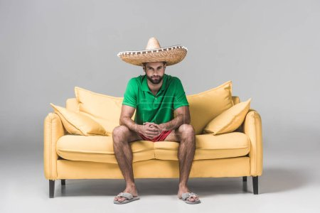 Photo for Handsome bearded man in mexican sombrero on yellow sofa on grey - Royalty Free Image