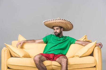 handsome mexican man in sombrero on yellow sofa on grey