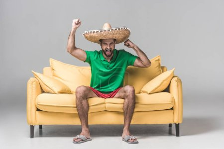 Photo for Handsome man in mexican sombrero yelling and celebrating triumph on yellow sofa on grey - Royalty Free Image