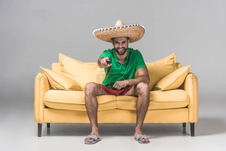 smiling bearded man in mexican sombrero watching TV with remote control on yellow sofa on grey