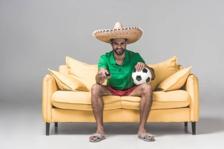 man in mexican sombrero watching match while sitting on yellow sofa with soccer ball and remote control on grey