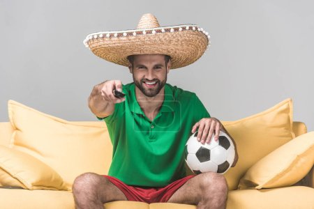 smiling man in mexican sombrero watching football match while sitting on yellow sofa with ball and remote control on grey
