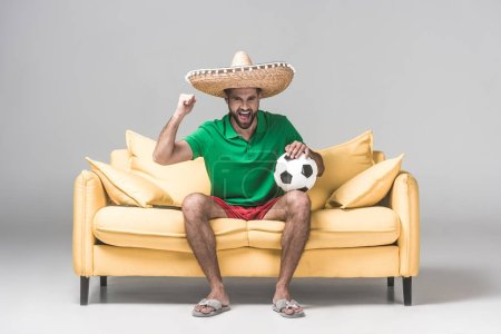 cheerful man in mexican sombrero watching soccer match while sitting on yellow sofa with ball on grey