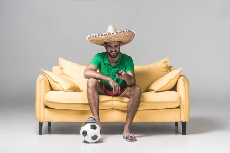 handsome mexican man in sombrero watching football match while sitting on yellow sofa with ball and remote control on grey