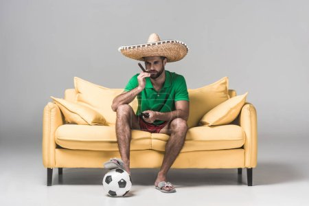 serious man in mexican sombrero watching soccer match while sitting on yellow sofa with cigar, ball and remote control on grey