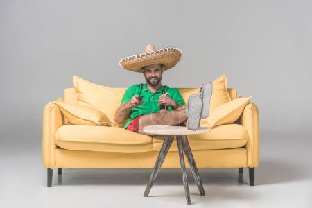 happy man in mexican sombrero with bottle of beer watching TV on yellow sofa on grey
