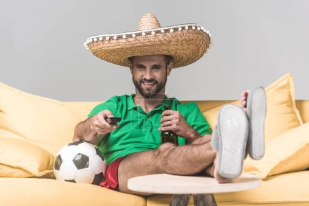 Photo for Smiling man in mexican sombrero watching football match while sitting on yellow sofa with ball, bottle of beer and remote control on grey - Royalty Free Image