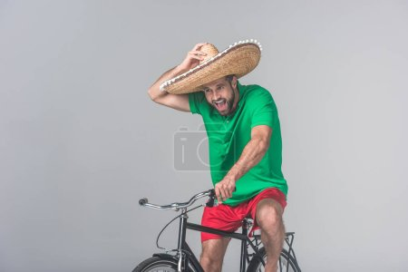 excited man in mexican sombrero riding bicycle on grey