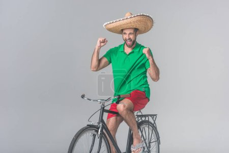 cheerful man in mexican sombrero celebrating and sitting on bike on grey