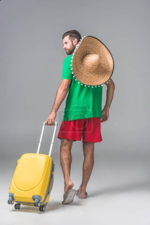 back view of male tourist in mexican sombrero walking with travel bag on grey