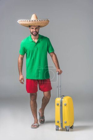 smiling traveler in mexican sombrero standing with suitcase on grey