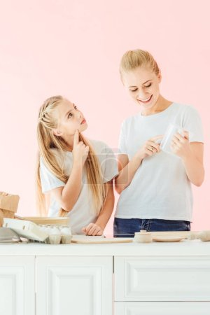 Photo for Beautiful mother and daughter in white t-shirts cooking together isolated on pink - Royalty Free Image