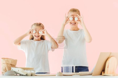 smiling young mother and daughter in white t-shirts covering eyes with chicken eggs while cooking isolated on pink