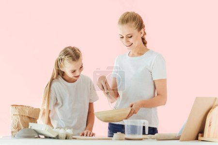 happy mother and daughter in white t-shirts looking at bowl while cooking together isolated on pink
