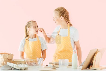 mother and daughter playing with flour while preparing dough isolated on pink