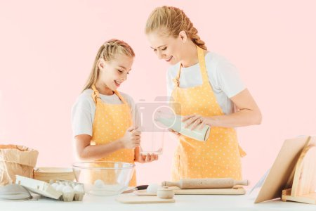 young mother pouring milk for preparing dough with daughter isolated on pink