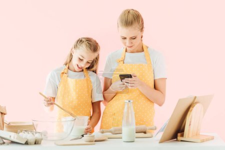 smiling mother and daughter using smartphone while cooking together isolated on pink