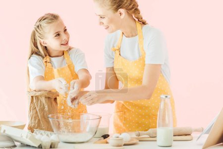 attractive young mother teaching daughter how to knead dough isolated on pink
