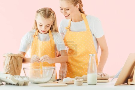 smiling young mother teaching daughter how to knead dough isolated on pink