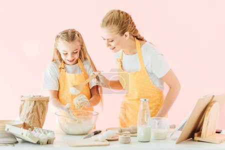 happy young mother and adorable little daughter in yellow aprons making dough together isolated on pink