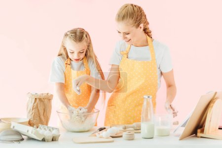 smiling young mother and adorable little daughter in yellow aprons making dough together isolated on pink