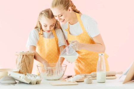Photo for Happy mother pouring milk into dough while daughter kneading isolated on pink - Royalty Free Image