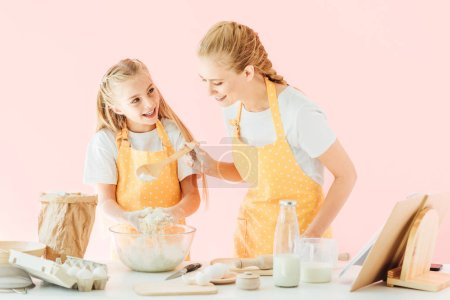 smiling young mother and adorable little daughter in yellow aprons kneading dough together isolated on pink
