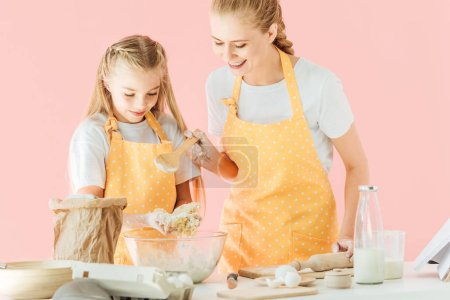 young mother and adorable little daughter in yellow aprons kneading dough together isolated on pink