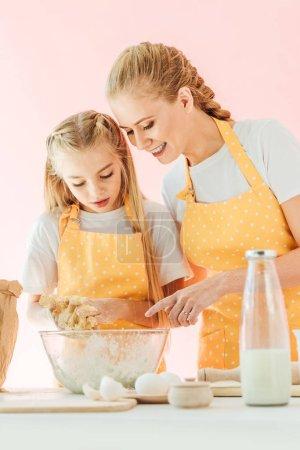 Photo pour Heureuse mère fille apprendre à pétrir la pâte isolé sur rose - image libre de droit